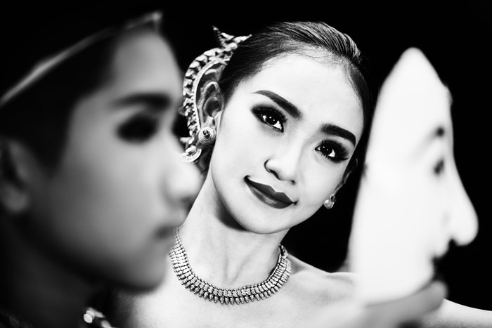Black and white portrait of a girl in traditional costume smiling towards the camera, framed by a blurred figure in the foreground holding a mask, black and white photography