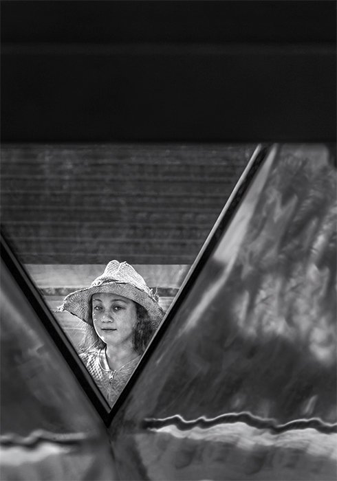 Black and white photo of a girl in white hat framed by architectural detail. Creative street photography