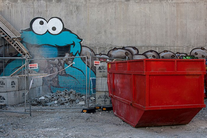 Graffiti of cookie monster character on a wall behind a building site. Creative street photography
