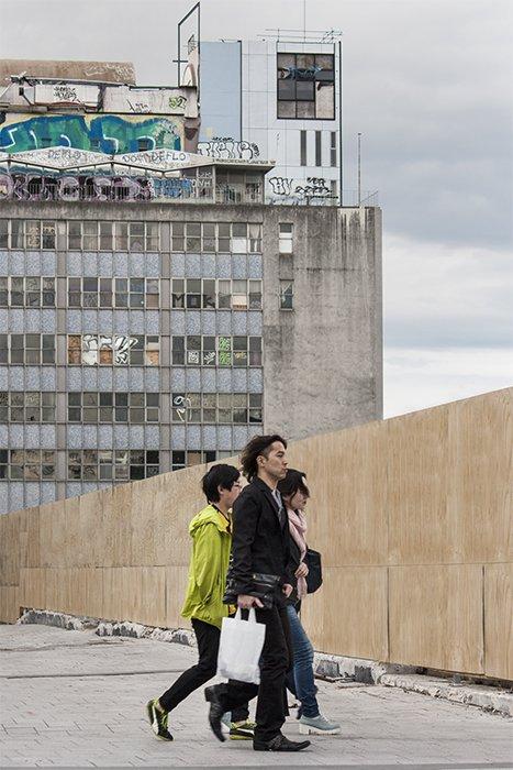 Street photo of three people walking past an apartment block. Creative street photography