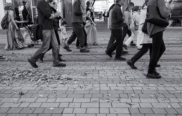Black and white street photo of a group of people walking. Creative street photography