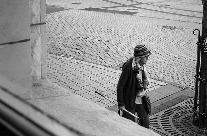 Black and white photo of a woman in framed taken from inside a window. Creative street photography