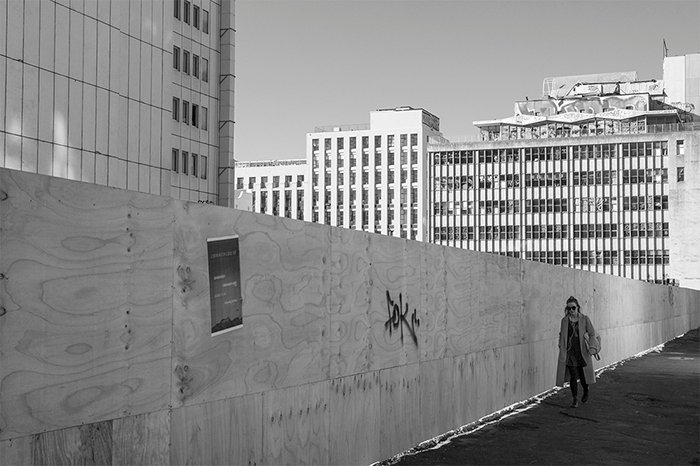 Black and white street photo of a city worker walking past an empty building site.. Creative street photography