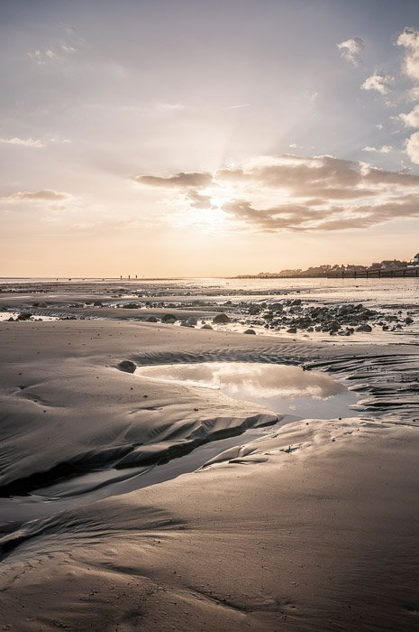 beautiful sunset photo on a sandy, rocky beach, the sky reflected in the waterpools