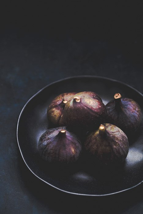 Food photography of a bowl of fresh figs against a dark background.
