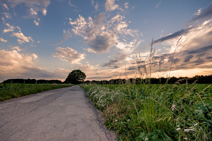 A compelling sunset over a countryside road and fields