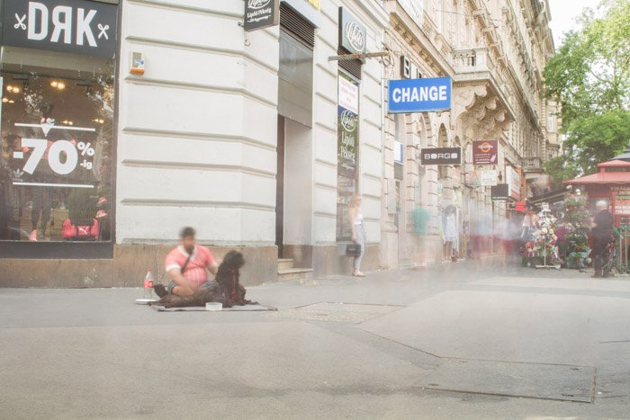 A long exposure street photograph in Budapest, a blurred homeless man sits on the ground with blurred figures in the background.