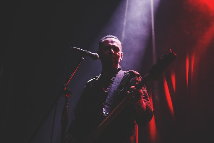 Moody shadowy portrait of a guitar player onstage during a performance. Improve your photography skills today.