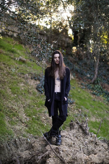 Portrait of a man with long hair, black clothes and tattooed chest, standing in a forest area, looking at the camera. Improve your photography skills today.