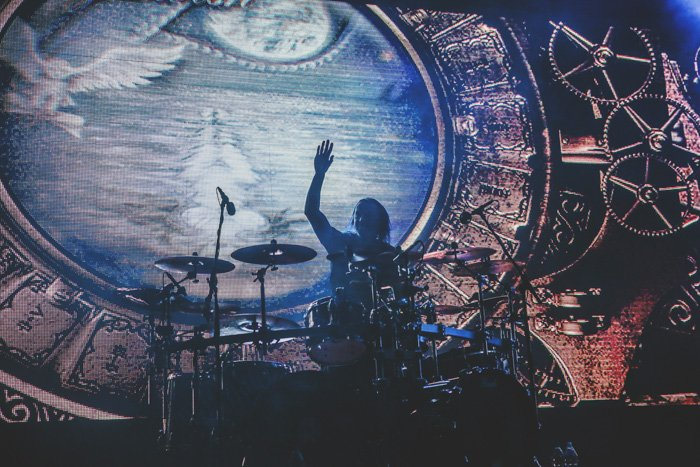 Photo of a drummer during a live concert, painted or projected gothic background. Improve your photography skills today.