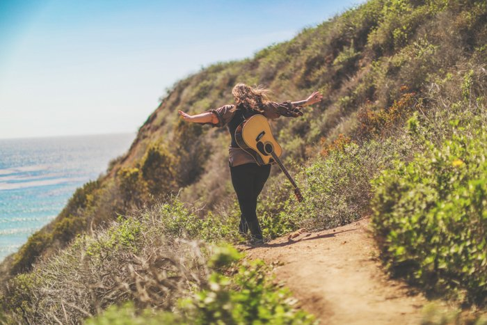 Outdoor photo of a person with acoustic guitar on their back, walking away from the camera on a coastal path, arms outstretched. Improve your photography skills today.