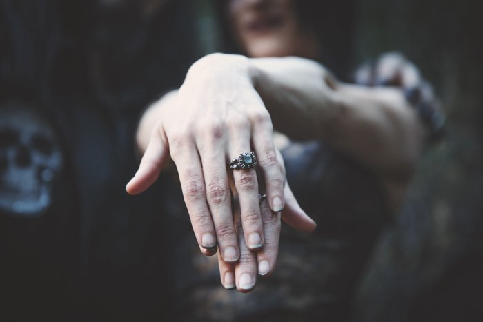 Close up of a girls hands clasped together, shadowy moody background. Improve your photography skills today.