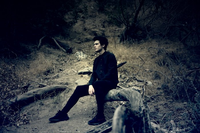 Dark and moody photo portrait of a man in black sitting on a low branch in a forest. Improve your photography skills today.