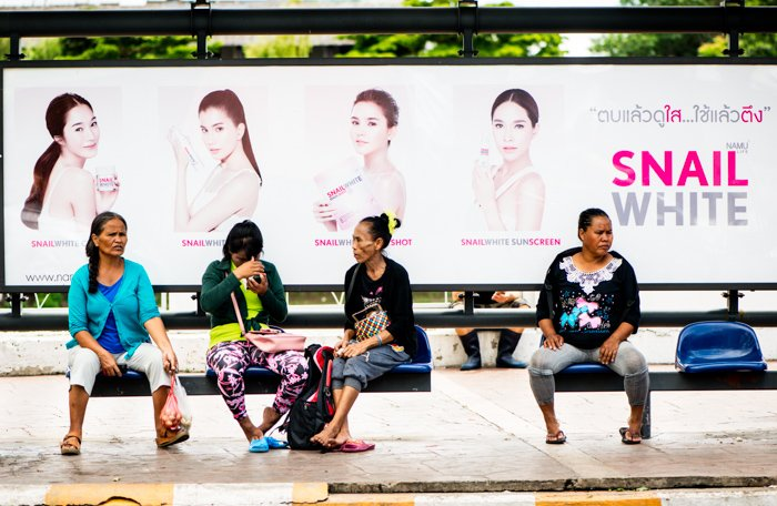 Documentary photography of four Thai women, waiting for a bus, a large advertising billboard behind them