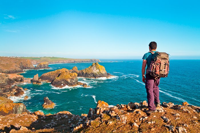 A male backpacker standing on rocky cliffs overlooking a fantastic seascape