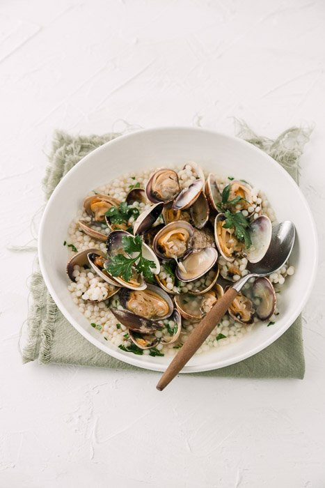 Overhead food photography of clams in a white bowl on white background.