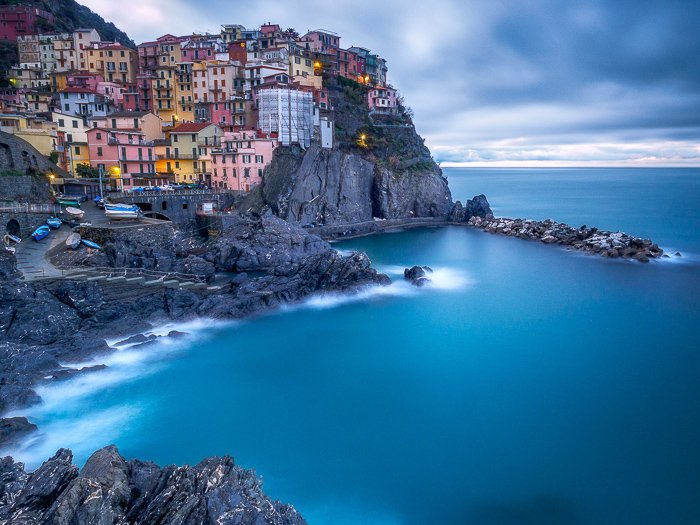 Long-exposure photo of a coastal town and seascape in Manarola at sunset.