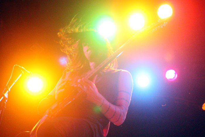 Colourful concert photography of a guitar player from low angle.