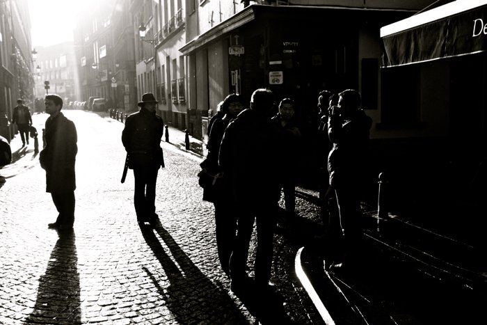Black and white street photography of a group of people talking.