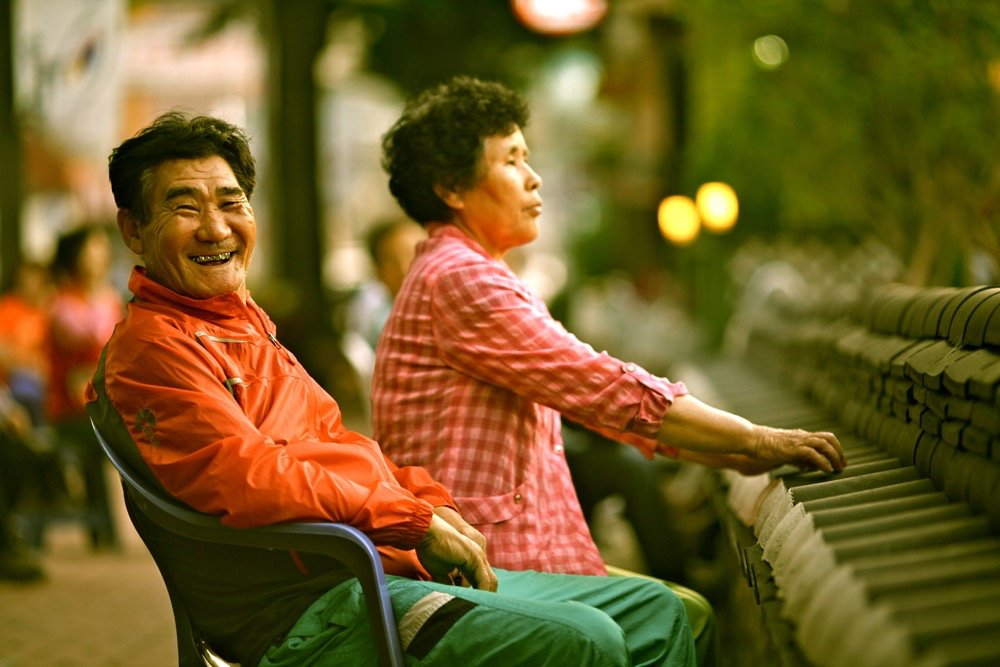 Street Photography of a man and woman sitting outdoors.