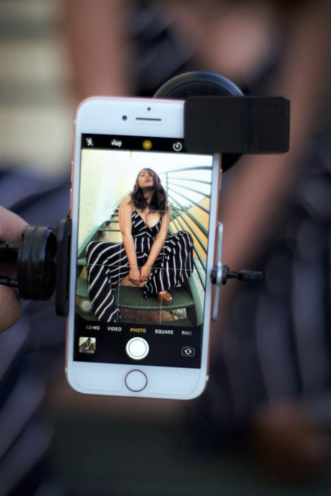 Smartphone with an image of a girl posing on the screen, held by a a smartphone tripod holder - ergonomic phone set-up for smartphone fashion photograph