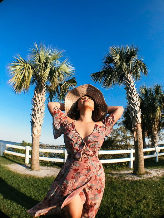 Girl in pink flowery dress and straw hat standing on the grass in front of a white fence and palm trees, holding her arms behind her head on a bright day - Smartphone fashion photography shoot