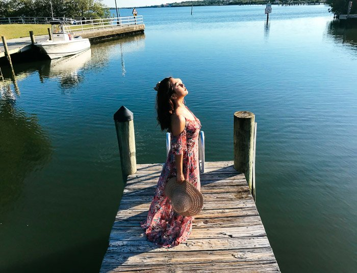 Girl in pink flowery dress and straw hat standing on a wooden dock by the sea, holding her hat behind by her side on a bright day - Smartphone fashion photography shoot
