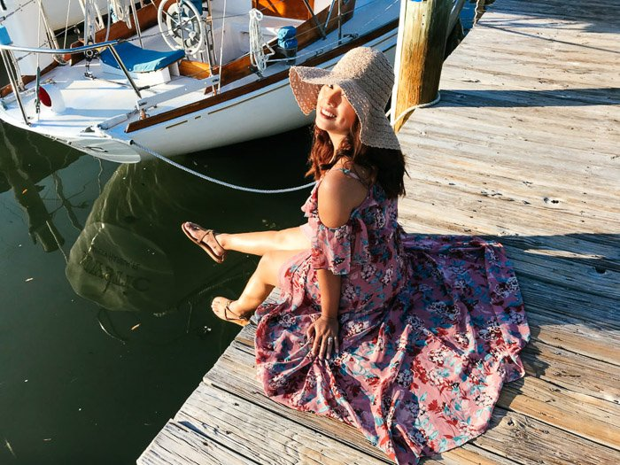 A girl in flowery dress and straw hat sits on a dock beside a boat, smiling at the camera. Location is important for Smartphone fashion photography