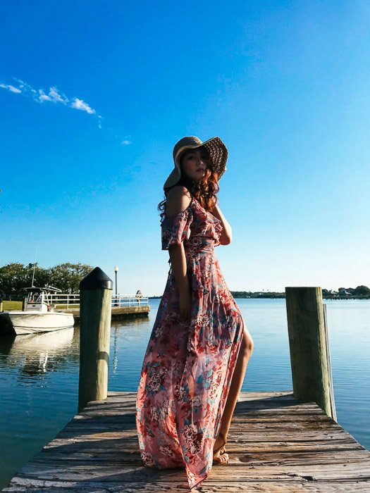 Girl in a long flowery dress and straw-hat standing on a wooden dock on a bright day, blue water and skies in the background. Smartphone fashion photography