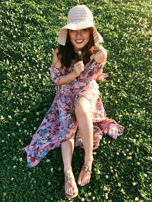 Girl in pink flowery dress and straw hat sitting on the grass and holding a white flower under her chin on a bright day at a smartphone fashion photography shoot