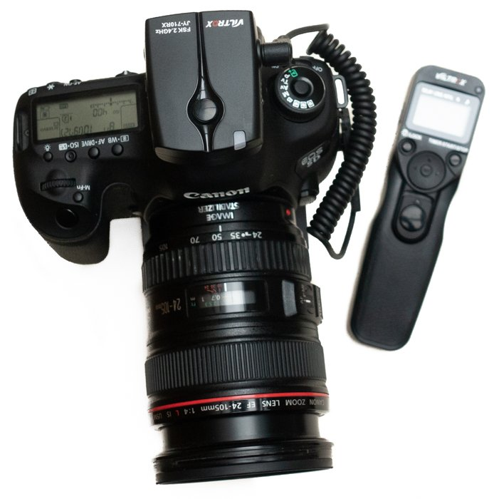 Canon camera with a separate intervalometer accessory on white background.