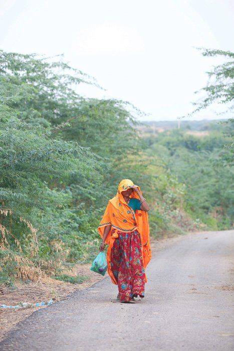 Travel photography of a woman in orange and red clothes walking down a down in India.