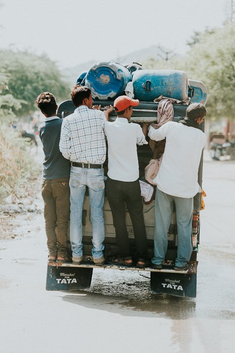 Travel photography of a group of men holding onto the back of a trailer in India.