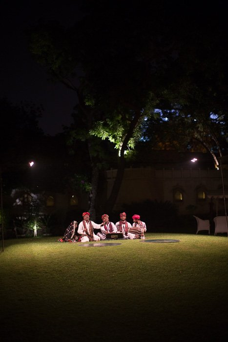 Travel photography of 4 men sitting on the grass under a tree at night.