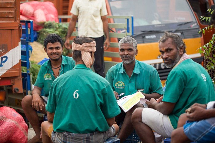 Travel photography of 4 men in green sitting in a flower market in India.