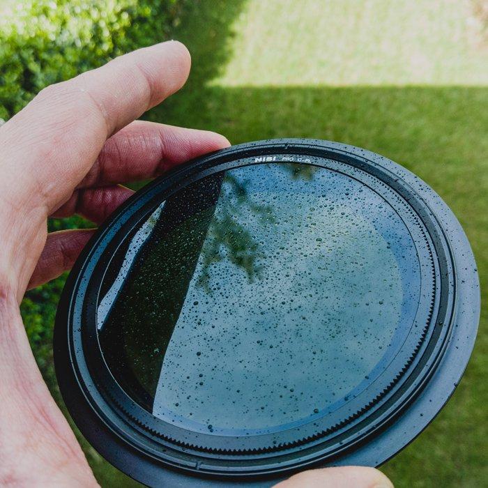 Close up of a hand holding a rain splattered camera lens filter
