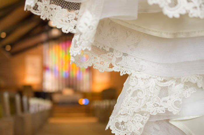 Detail of a wedding dress in foreground of a church interior