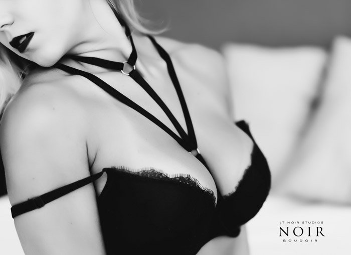 black and white boudoir photo portrait of a blonde girl wearing black bra and neck harness