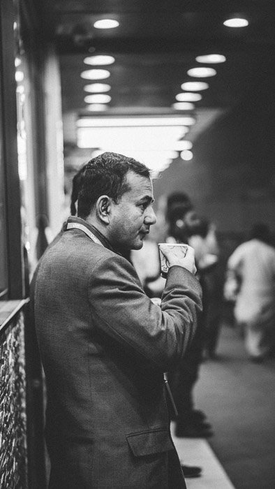 Black and white street photo of a man drinking coffee. Low light photography.