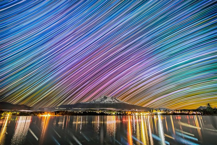 Stunning landscape image of a brightly coloured long exposure sky over a mountain and water. Low light photography.