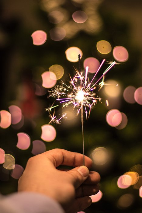Macro image of a hand holding a lit sparkler at night. Low light photography.