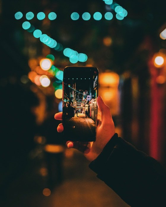 A hand holding a smartphone to naturally frame a night street photo , using a Wide and Shallow Depth of Field Together
