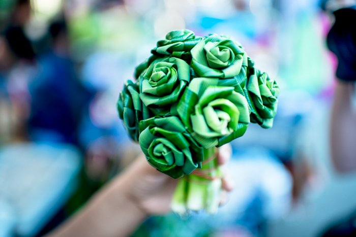 Close up of a hand holding a bunch of green handmade craft flowers, blurry background. Documentary photography.