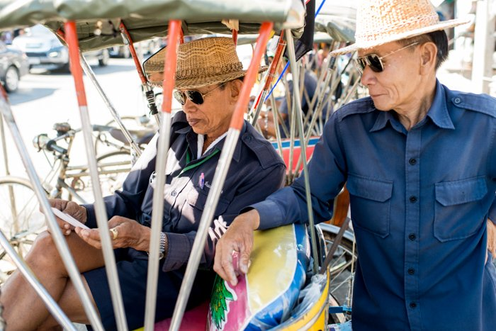 Documentary photography portrait of two men in straw hats and sunglasses in a Market in Chiang Mai, Thailand.