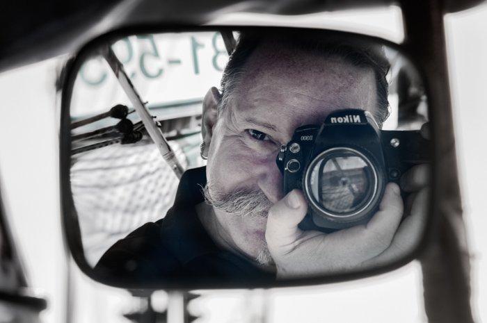 The photographer taking a selfie through a car mirror. Documentary photography.