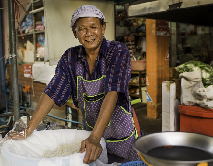 Documentary photography portrait of a sticky rice vendor at Muang Mai Market, Chiang Mai, Thailand