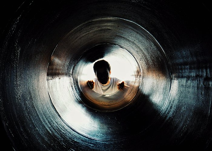 A faceless portrait of a man looking up through a dark tunnel
