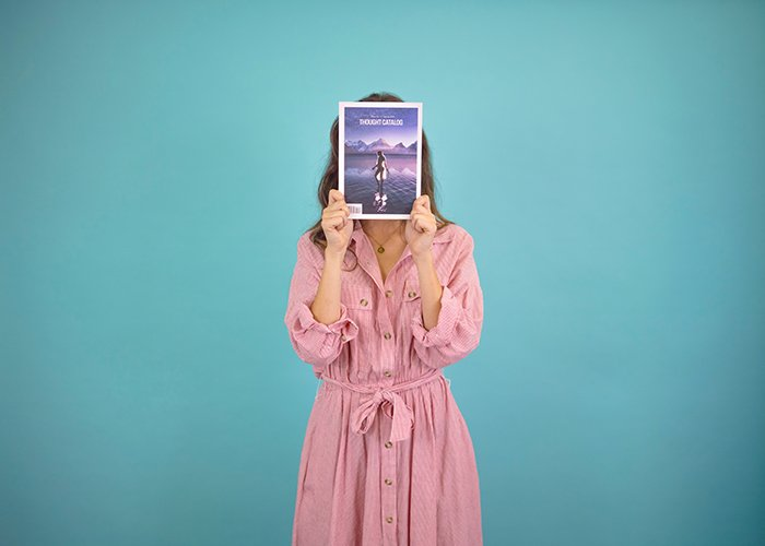 A woman in pink using a magazine to create a faceless portrait to advertise her business