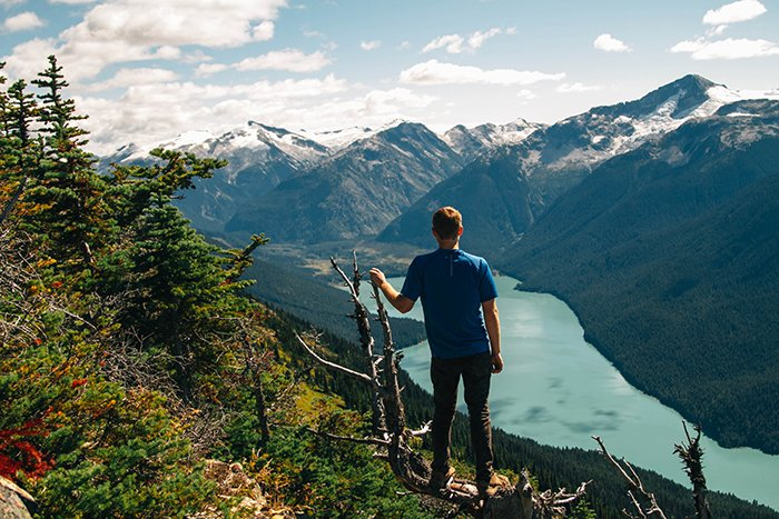 A man is blue t-shirt standing in the foreground of a mountainous landscape with his back turned to the camera