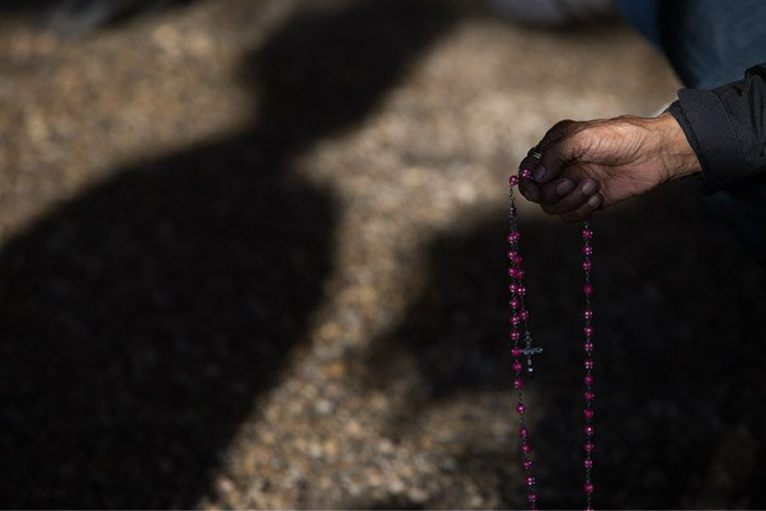 a hand holding rosary beads against a shadowing background. Photo by Amber Bracken.